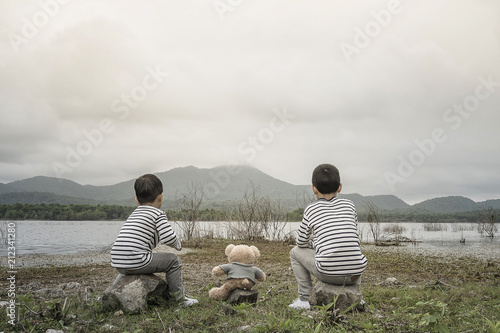 Fantastique Paysage child asian with teddy bear sitting site the reservoir is the background.