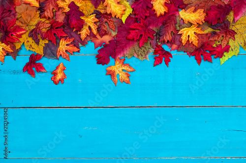Valokuva  Blank antique rustic teal blue background with colorful autumn leaves border; wo