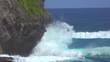 SLOW MOTION, CLOSE UP: Beautiful foaming turquoise ocean waves crash into the black cliff on the sunny coasts of Bali. Beautiful shot of tube waves breaking and splashing glassy water everywhere.