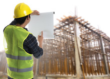 Construction Concept,Asian Engineer Man Holding Blue Print Paper Inspecting At Construction Site