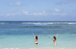 Summer holidays and vacation - happy young girls sunbathing on the beach in sea having fun