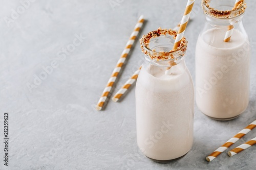 Foto op Aluminium Milkshake Vanilla milkshake in glass bottles on a gray background