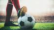 Leinwandbild Motiv feet of soccer player tread on soccer ball for kick-off in the stadium