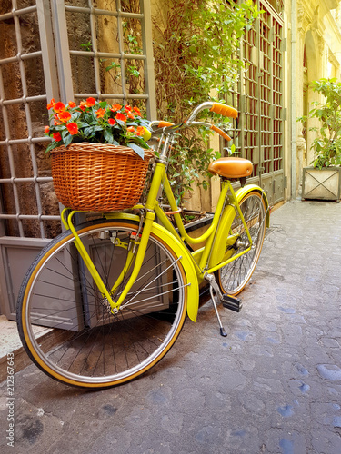 Papiers peints Velo Colorful yellow bicycle parked on the old narrow street in Rome, Italy