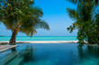 Tropical landscape, swimming pool and turquoise ocean. Palms around the pool. Maldives vacation.