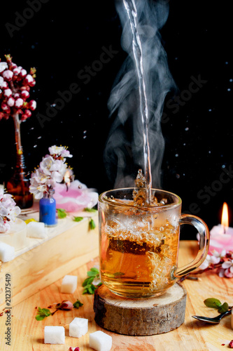 Staande foto Thee Hot aromatic tea with splashes on a cup with flowers on the table