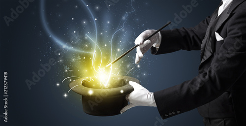 Fotografia Magician hand conjure with wand  light from a black cylinder