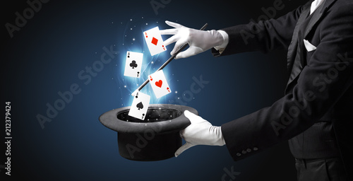 Foto Magician with white gloves conjuring playing cards from a cylinder with magic wa