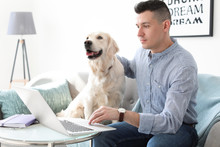 Portrait Of Owner With His Friendly Dog Using Laptop At Home