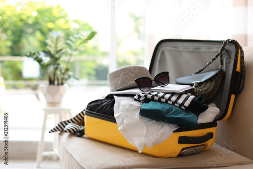 Fototapeta Open yellow suitcase with different clothes packed for journey at home obraz
