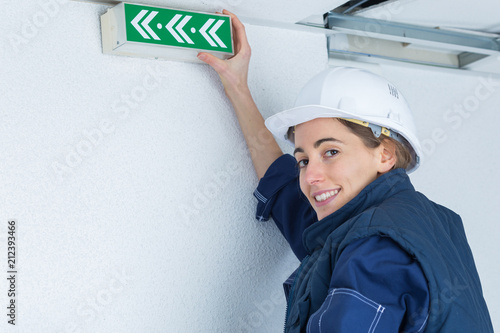 Foto Woman holding directional exit arrow sign on wall