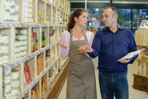 Manager instructing worker in store Wallpaper Mural