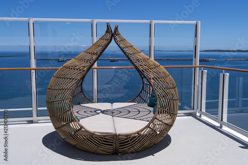 rattan chaise lounges on the deck of a luxury cruise ship