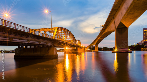 Foto op Plexiglas Brug Metal bridge crossing river night view with reflection light