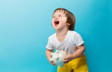 Toddler Boy With A Piggy Bank On A Blue Background