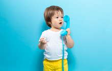 Toddler Boy With An Old Fashioned Phone On A Blue Background
