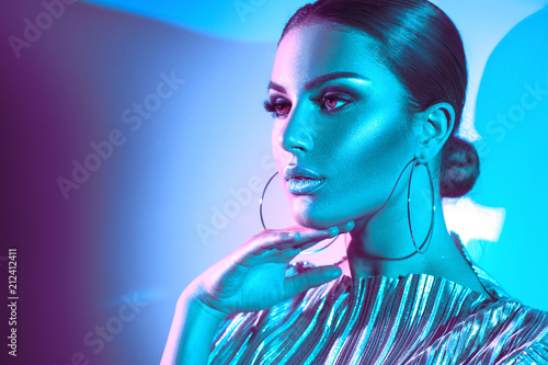 Poster Beauty Fashion model brunette woman in colorful bright neon lights posing in studio. Beautiful sexy girl, trendy glowing makeup, metallic silver lips