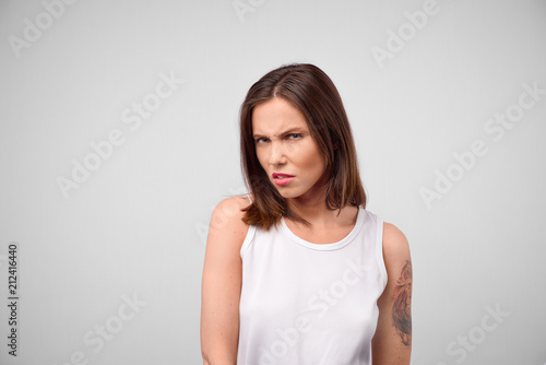 Fényképezés  Young woman with disgusted expression repulsing something