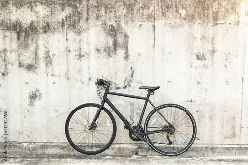 Staande foto Fiets Matt black race road bike parked in front of grunge textured background with vintage tone.