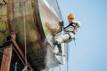 Industrial Climber Washing Big Barrel With Water Pressure. Risky Job.