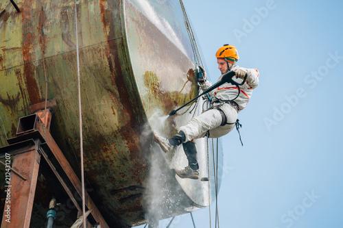 Fototapeta Industrial climber washing big barrel with water pressure