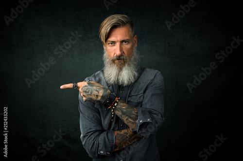 Fotografie, Obraz  Porträt eines bärtigen Geschäftsmannes, der mit seinem Finger Richtung rechte Se