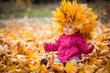 Leinwandbild Motiv Little kid is playing and sitting in fallen leaves in autumn park. Baby is in big wreath of leaves. Girl is dressed in warm hat, jacket.