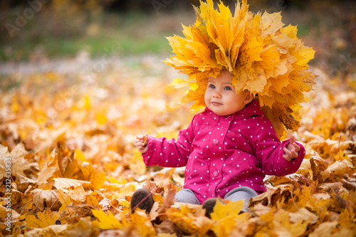 Obraz Little kid is playing and sitting in fallen leaves in autumn park. Baby is in big wreath of leaves. Girl is dressed in warm hat, jacket. - fototapety do salonu