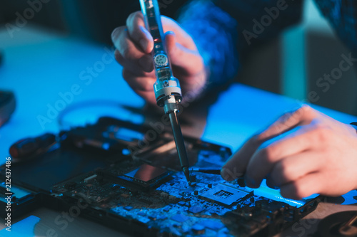 electronic recycle. gadgets repair. technician or engineer soldering used or broken motherboard.