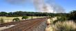 Schienenstrang in wundervoller Landschaft mit riesigen Wolken eines Waldbrandes am Horizont