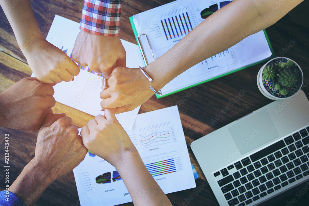 Fototapeta Meeting teamwork concept,Friendship,Group people with stack of hands showing unity after successful negotiations at office