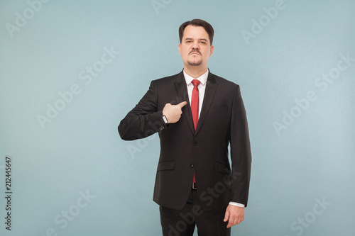 Foto op Plexiglas Artist KB Man in classic wear pointing himself at camera. I did it and I'm proud of it. indoor studio shot. isolated on light blue background. handsome businessman with black suit, red tie and mustache.