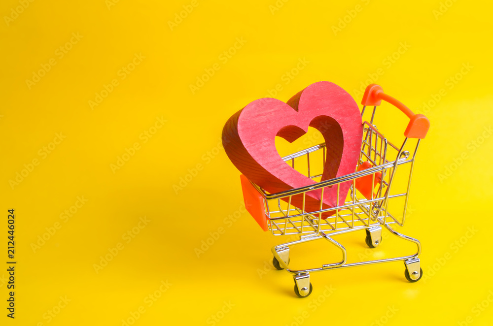 Fototapeta A supermarket trolley with a red heart inside. Love of shopping and shopping. Favorite store or supermarket. Buy love and happiness. Shopaholics, consumer society. Intimate services for money