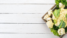 Cauliflower In A Wooden Box. Fresh Vegetables. On A Wooden Background. Top View. Copy Space.