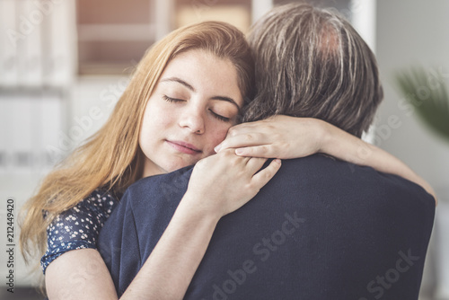 Photo  Young daughter hugs her father