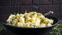 Warm Potato Salad With Gherkins In A Black Plate