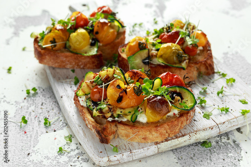 Photographie Healthy toasts with baked sweet cherry tomatoes and grilled zucchinin ribbons dr