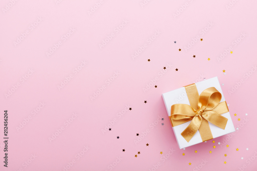 Fototapeta Gift or present box and stars confetti on pink table top view. Flat lay composition for birthday, mother day or wedding.