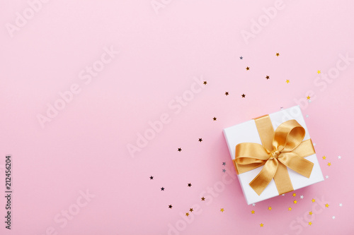 Foto Gift or present box and stars confetti on pink table top view