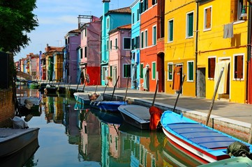 Fototapeta na wymiar Canal with colorful buildings and houses in Burano island, Venice, Italy - Famous Architecture and landmarks