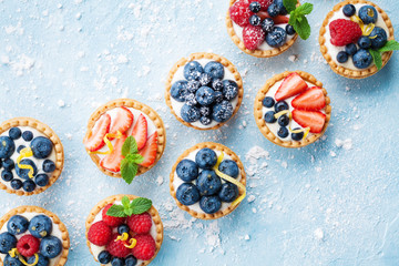 Fototapeta Healthy summer pastry dessert. Berry tartlets or cake with cream cheese top view.