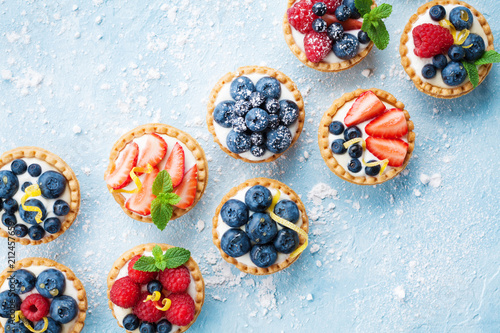 Poster Dessert Healthy summer pastry dessert. Berry tartlets or cake with cream cheese top view.