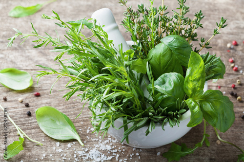 Papiers peints Condiment Aromatic herbs in mortar bowl. Basil, thyme, rosemary and tarragon. Fresh ingredients for cooking.