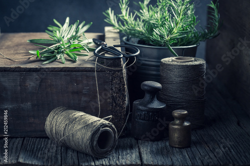 Keuken foto achterwand Aromatische Green rosemary, string and weights on a wooden box