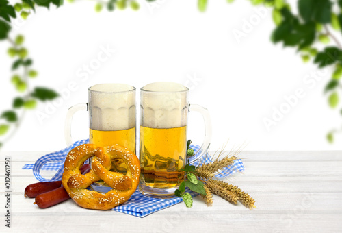 Foto op Aluminium Bier / Cider Bavarian pretzels, wheat ears, sausages, mugs of lager beer, hop and blue and white doily and ribbon on white wooden table on white background with green hop with space for text. Oktoberfest