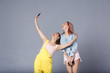 Portrait of lovely overjoyed having fun and grimacing while taking selfie using mobile phone, posing against gray wall background. Two happy young women spending fun time together. Electronic gadget
