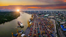 Aerial View Of International Port With Crane Loading Containers In Import Export Business Logistics With Cityscape Of Bangkok City Thailand At Sunset