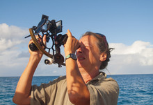 Navigator On Board Of A Sailing Yacht Using A Sextant As Traditional Method Of Navigation