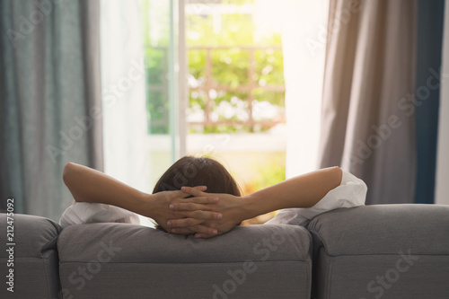 Poster Relaxation Young woman relaxing on sofa at cozy home and looking outside in living room