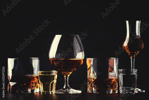 Foto op Aluminium Bar Set of strong alcoholic drinks in glasses and shot glass in assortent: vodka, rum, cognac, tequila, brandy and whiskey. Dark vintage background, selective focus
